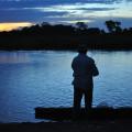 Pescador se arrisca às margens do rio cheio de Jacarés.